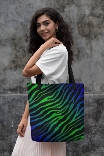 Woman holding a blue/green Ripped Spacetime Stripes tote bag.