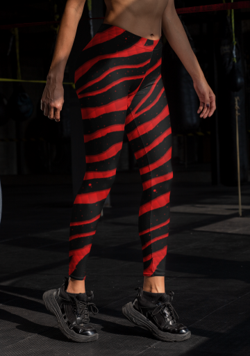 Woman wearing red Ripped Spacetime Stripes leggings.