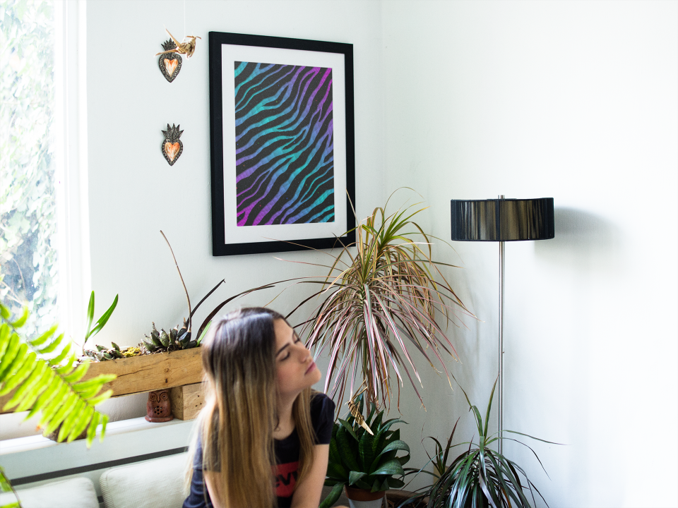 Woman sitting in a waiting room near a pink/cyan Ripped Spacetime Stripes art print.