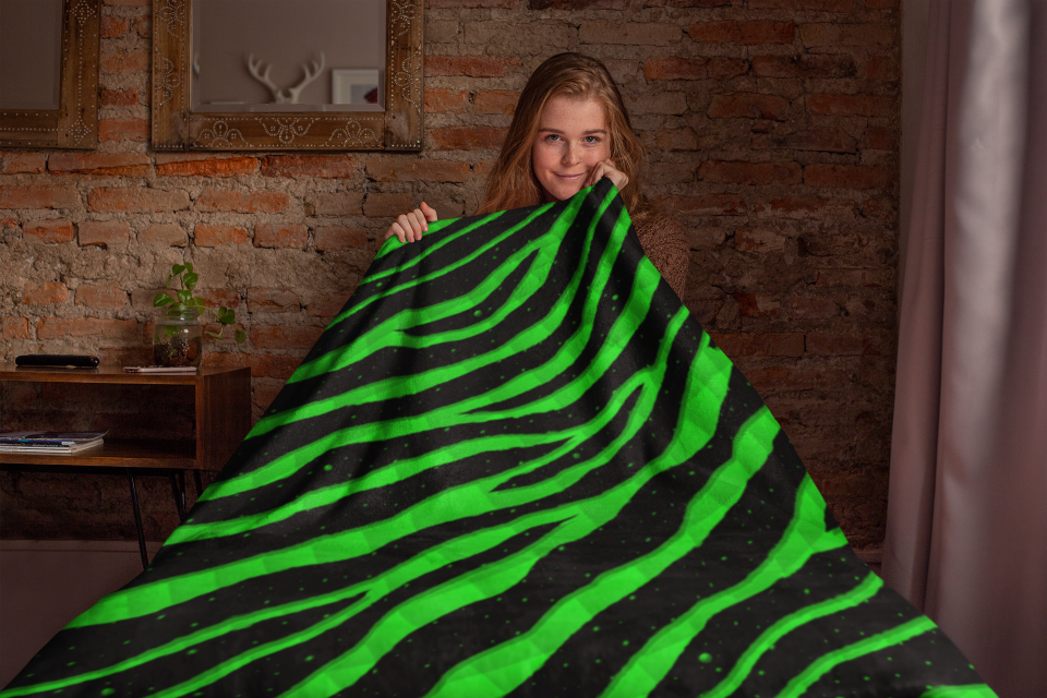Woman sitting under a green Ripped Spacetime Stripes throw blanket.